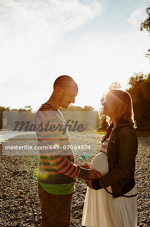 Pregnant woman and partner standing face to face beside river holding windmill Stock Photo - Premium Royalty-Free, Image code: 649-07064574