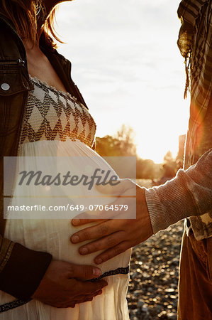 Midsection of pregnant woman and partner touching bump Stock Photo - Premium Royalty-Free, Image code: 649-07064579