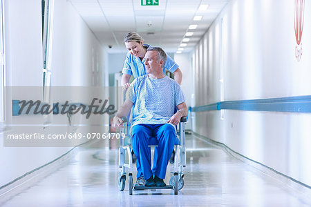 Nurse pushing patient in wheelchair down corridor Stock Photo - Premium Royalty-Free, Image code: 649-07064709