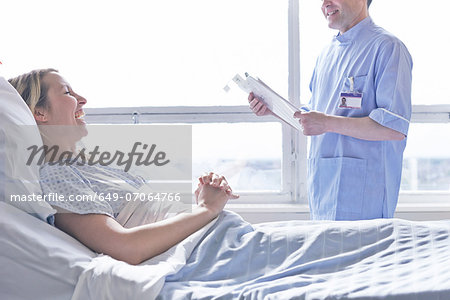 Patient lying in hospital bed laughing with nurse Stock Photo - Premium Royalty-Free, Image code: 649-07064766