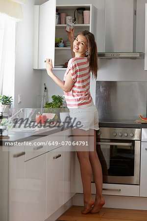 Woman taking mug from cabinet Stock Photo - Premium Royalty-Free, Image code: 649-07064791