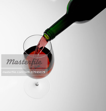 Pouring red wine into glass Stock Photo - Premium Royalty-Free, Image code: 649-07065079