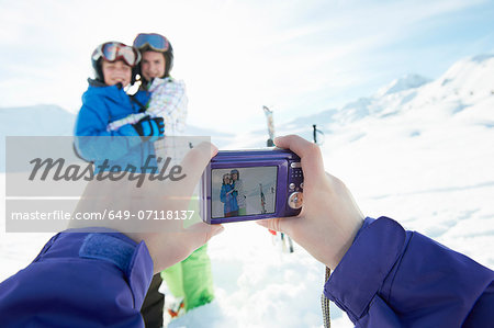Sister photographing siblings in snow, Les Arcs, Haute-Savoie, France Stock Photo - Premium Royalty-Free, Image code: 649-07118137
