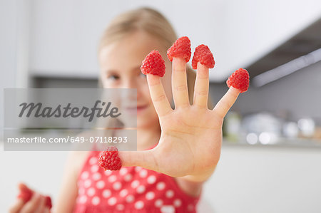 Girl putting raspberries on fingers Stock Photo - Premium Royalty-Free, Image code: 649-07118293