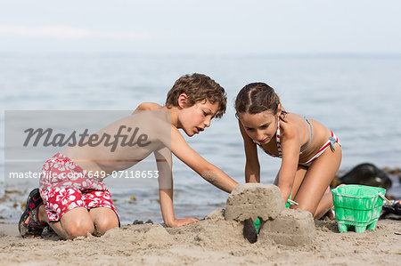 Brother and sister on beach building sandcastle Stock Photo - Premium Royalty-Free, Image code: 649-07118653