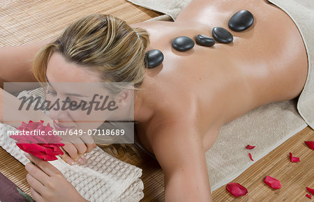 Woman enjoying a hot stone treatment Stock Photo - Premium Royalty-Free, Image code: 649-07118689