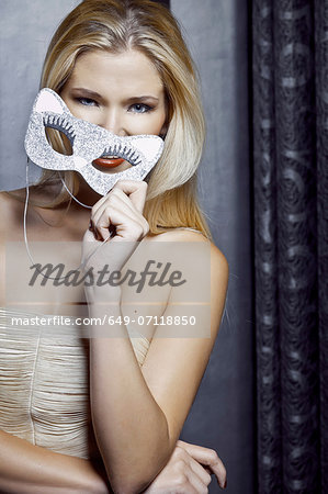 Portrait of young woman holding feline mask Stock Photo - Premium Royalty-Free, Image code: 649-07118850