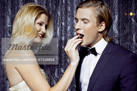 Young woman giving chocolate to boyfriend Stock Photo - Premium Royalty-Free, Image code: 649-07118858