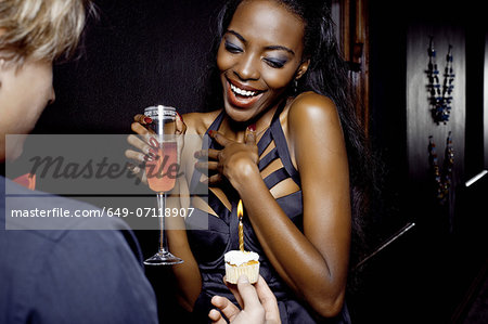 Young woman getting birthday cake in nightclub Stock Photo - Premium Royalty-Free, Image code: 649-07118907
