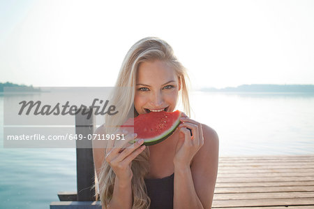 Portrait of young woman at lake eating watermelon Stock Photo - Premium Royalty-Free, Image code: 649-07119051