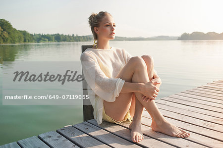 Young woman sitting on lake pier Stock Photo - Premium Royalty-Free, Image code: 649-07119055
