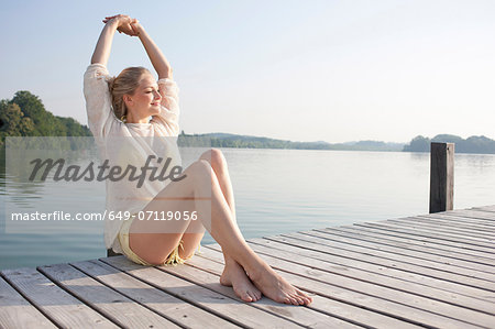 Young woman relaxing on lake pier Stock Photo - Premium Royalty-Free, Image code: 649-07119056