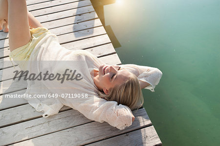 Young woman sunbathing on lake pier Stock Photo - Premium Royalty-Free, Image code: 649-07119058
