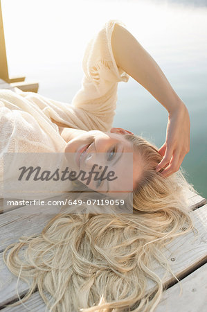 Young woman lying on lake pier Stock Photo - Premium Royalty-Free, Image code: 649-07119059