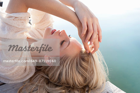 Close up of young woman lying on lake pier Stock Photo - Premium Royalty-Free, Image code: 649-07119060