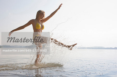 Young woman kicking water in lake Stock Photo - Premium Royalty-Free, Image code: 649-07119063