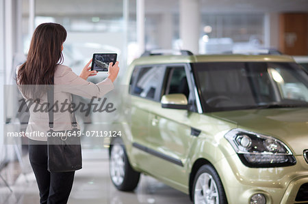 Mid adult woman taking photograph of car in showroom Stock Photo - Premium Royalty-Free, Image code: 649-07119124