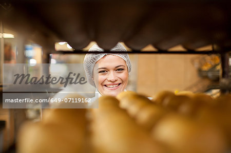 Portrait of young baker and tray of bread rolls Stock Photo - Premium Royalty-Free, Image code: 649-07119162