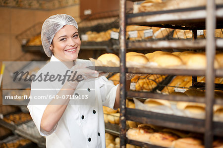 Portrait of young baker holding tray of bread rolls Stock Photo - Premium Royalty-Free, Image code: 649-07119163