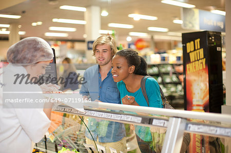 Young sales assistant at counter with customers Stock Photo - Premium Royalty-Free, Image code: 649-07119164
