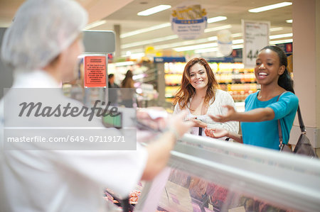 Young male sales assistant serving customers at counter Stock Photo - Premium Royalty-Free, Image code: 649-07119171
