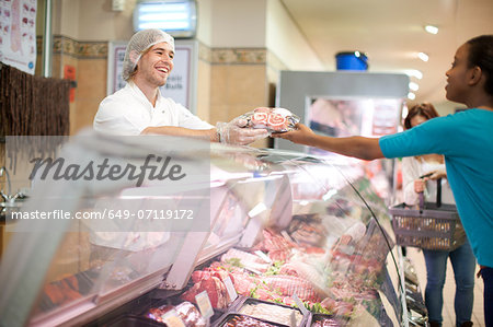 Young male sales assistant serving customer at counter Stock Photo - Premium Royalty-Free, Image code: 649-07119172