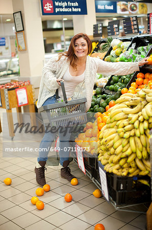 Young woman having shopping mishap with oranges Stock Photo - Premium Royalty-Free, Image code: 649-07119173