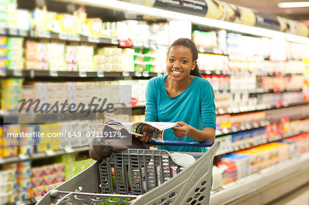 Female shopper with brochure in supermarket Stock Photo - Premium Royalty-Free, Image code: 649-07119179