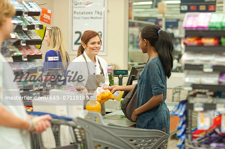 Female shop assistant at check-out Stock Photo - Premium Royalty-Free, Image code: 649-07119189