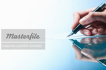 Close up of female hand writing on paper with ink pen Stock Photo - Premium Royalty-Free, Image code: 649-07119192