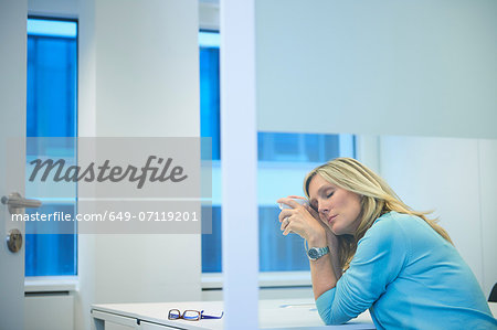 Tired businesswoman working late at office Stock Photo - Premium Royalty-Free, Image code: 649-07119201