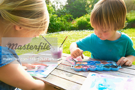 Brother and sister finger painting in garden Stock Photo - Premium Royalty-Free, Image code: 649-07119205