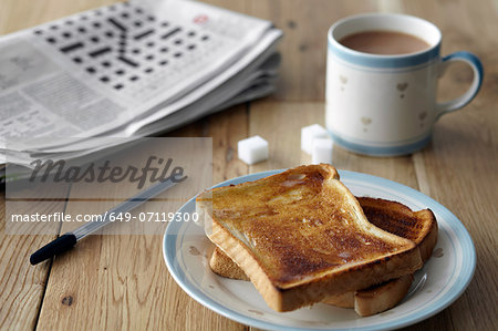 Kitchen table still life with crossword, toast and tea Stock Photo - Premium Royalty-Free, Image code: 649-07119300