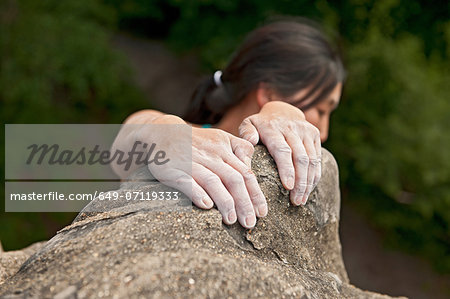 Woman hanging on to sandstone Stock Photo - Premium Royalty-Free, Image code: 649-07119333