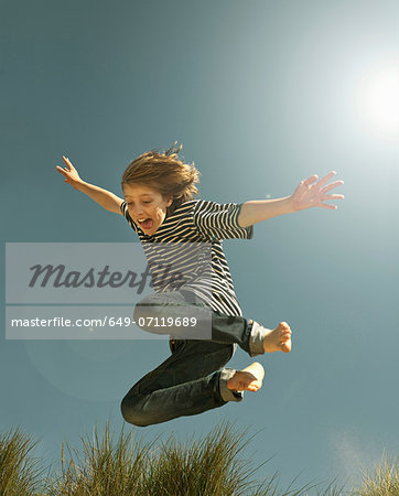 Teenage boy jumping against clear blue sky Stock Photo - Premium Royalty-Free, Image code: 649-07119689