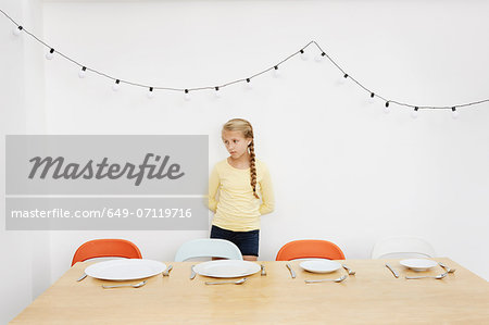 Girl waiting by table with empty plates Stock Photo - Premium Royalty-Free, Image code: 649-07119716