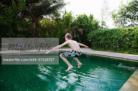 Boy jumping into swimming pool Stock Photo - Premium Royalty-Free, Image code: 649-07119727