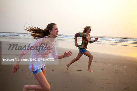 Mother and daughter running on beach Stock Photo - Premium Royalty-Free, Image code: 649-07119733