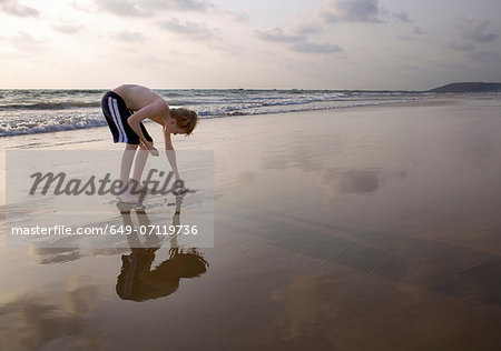Boy bending over touching sand on beach Stock Photo - Premium Royalty-Free, Image code: 649-07119736