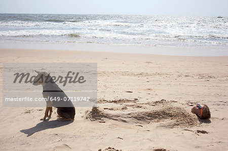 Boy buried in sand on beach with dog Stock Photo - Premium Royalty-Free, Image code: 649-07119742