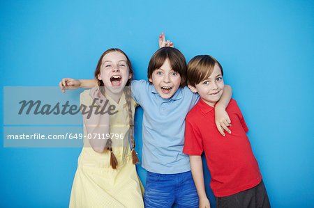 Portrait of three children with arms around each other against blue background Stock Photo - Premium Royalty-Free, Image code: 649-07119796