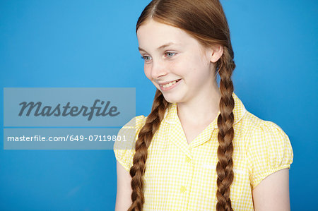 Portrait of girl with plaits wearing yellow school dress Stock Photo - Premium Royalty-Free, Image code: 649-07119801