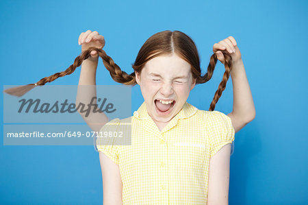 Girl wearing yellow school dress, boy behind pulling her plaits Stock Photo - Premium Royalty-Free, Image code: 649-07119802
