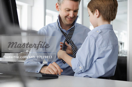 Son putting tie on father at desk Stock Photo - Premium Royalty-Free, Image code: 649-07119813