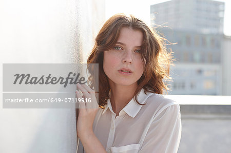 Portrait of young woman leaning against wall Stock Photo - Premium Royalty-Free, Image code: 649-07119916