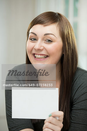 Happy young woman with a blank card Stock Photo - Premium Royalty-Free, Image code: 649-07238233