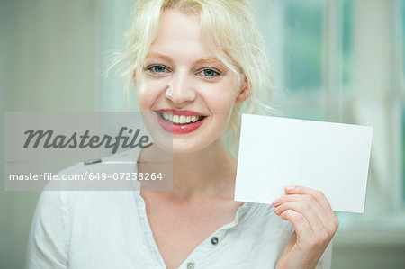 Young woman holding a blank card Stock Photo - Premium Royalty-Free, Image code: 649-07238264