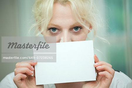 Young woman holding a blank card over her face Stock Photo - Premium Royalty-Free, Image code: 649-07238265