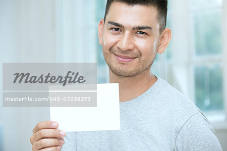Mid adult man holding a blank card Stock Photo - Premium Royalty-Free, Image code: 649-07238273