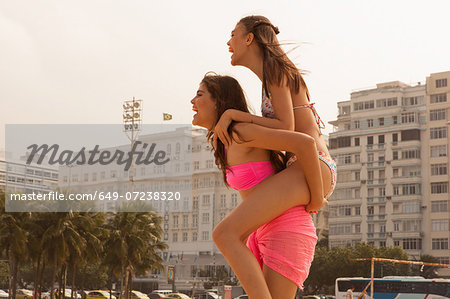 Young woman riding piggyback on friend, Copacabana Beach, Rio De Janeiro, Brazil Stock Photo - Premium Royalty-Free, Image code: 649-07238320